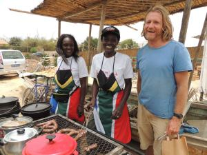 Rachel Oumou Sy and her sister, getting to grips with braaiing with tips from Sampson